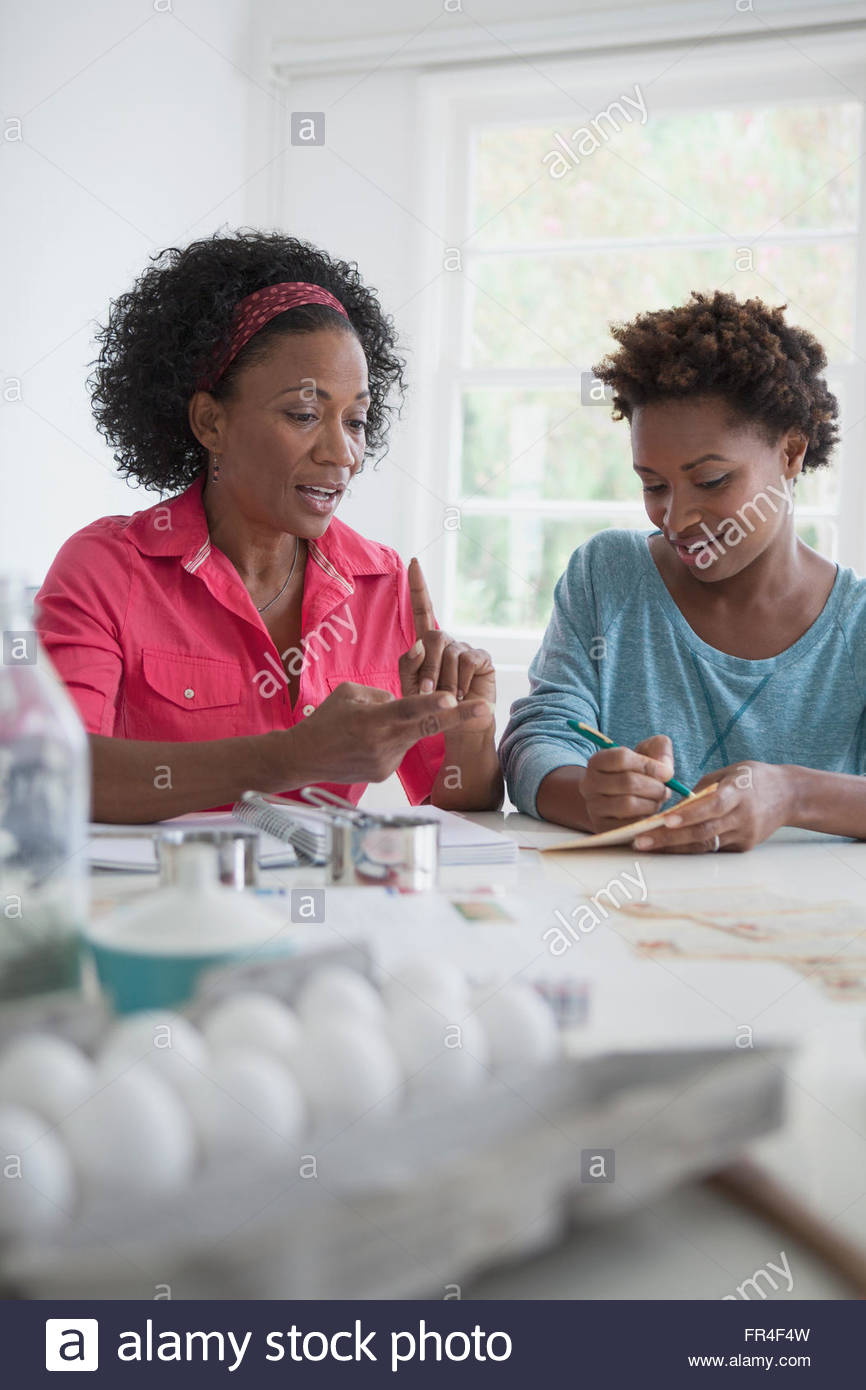 mother and daughter creating a shopping list from recipe - Stock Image