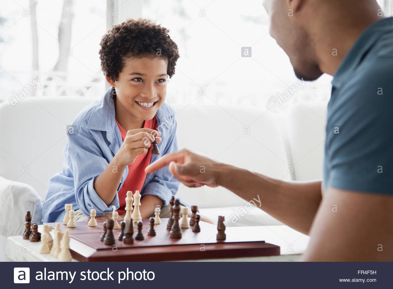 father and son challenging each other in a chess game - Stock Image