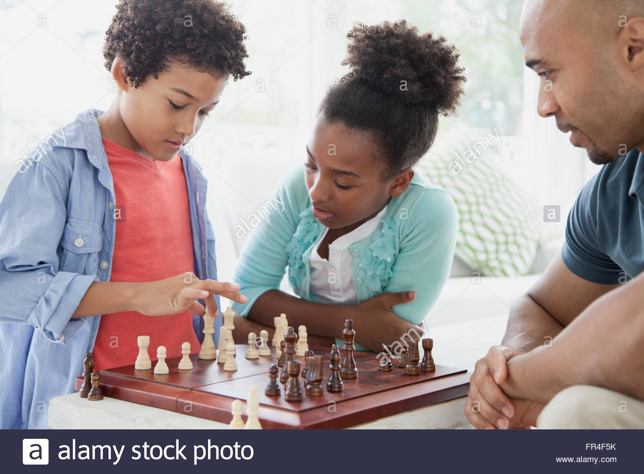 brother and sister playing a chess game - Stock Image