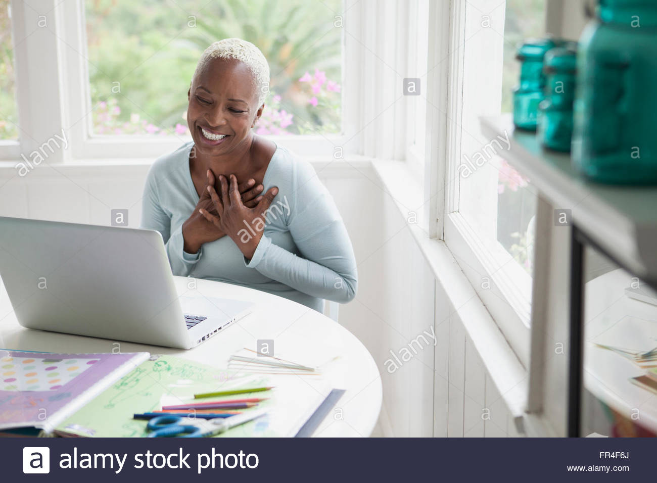 middle aged woman with hands over heart during online chat - Stock Image