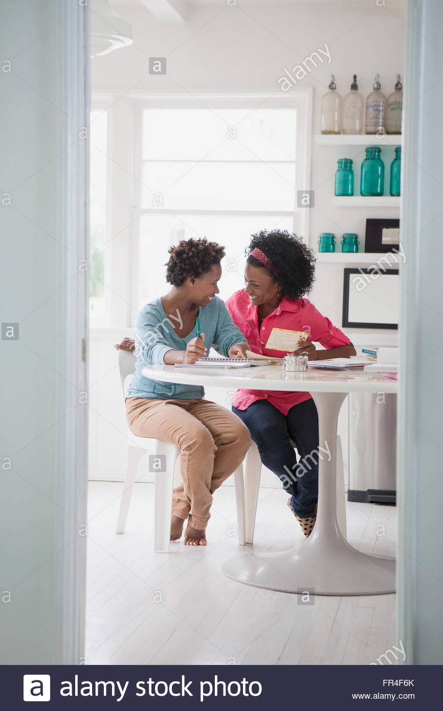 mother and daughter sharing a laugh in the kitchen Stock Photo
