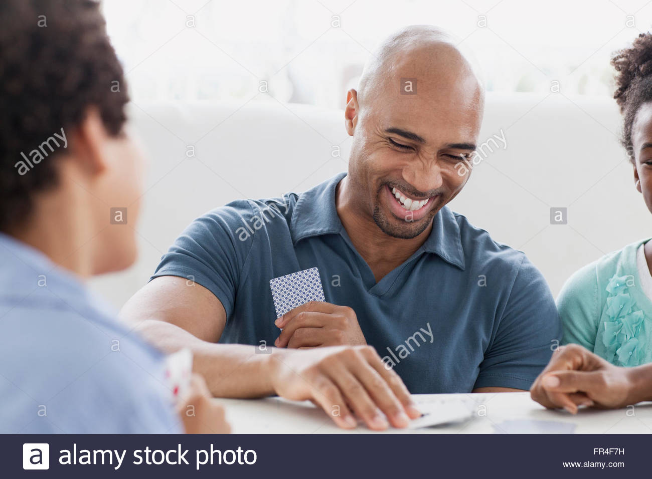 father laughing as he plays cards with son and daughter - Stock Image