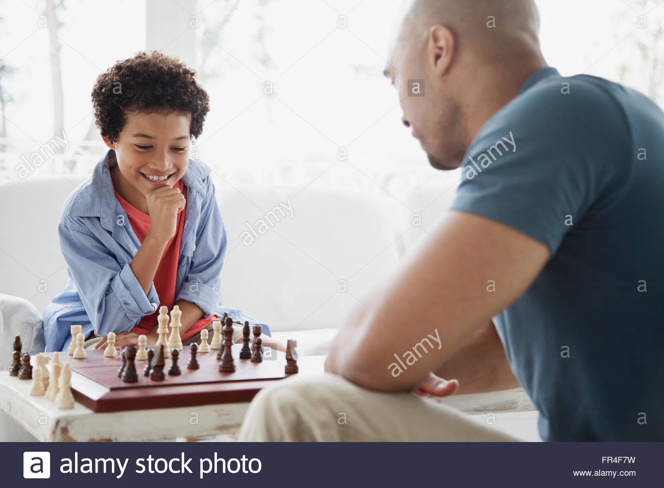 father and son enjoying a game of chess - Stock Image