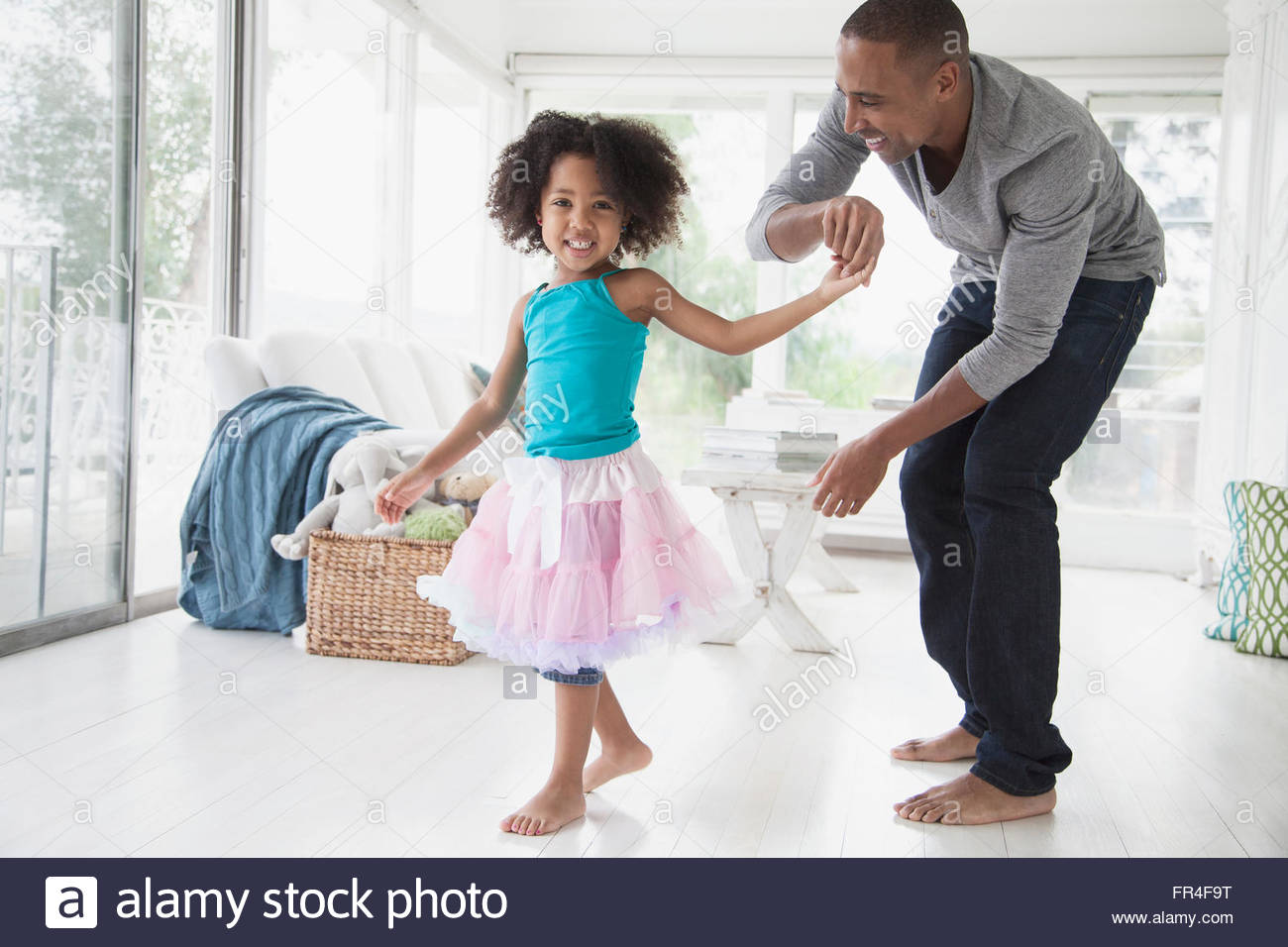 father twirling young daughter in sunroom - Stock Image