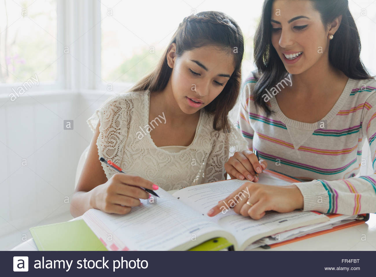 sister helping younger sister with homework - Stock Image