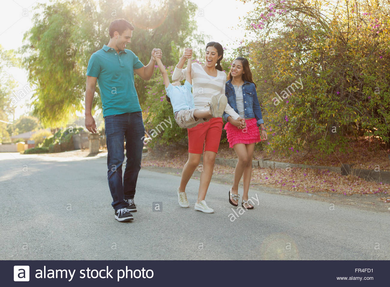 parents swinging young son while out for a walk - Stock Image
