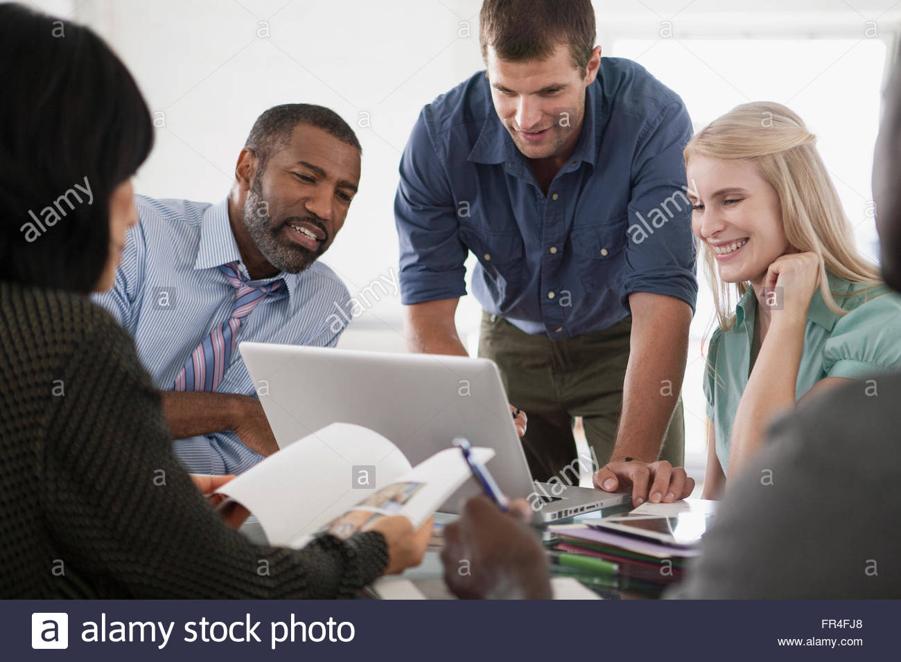 three people looking at laptop in business meeting - Stock Image