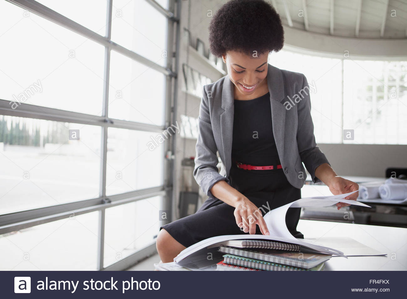 african american businesswoman smiling as she reviews paperwork - Stock Image