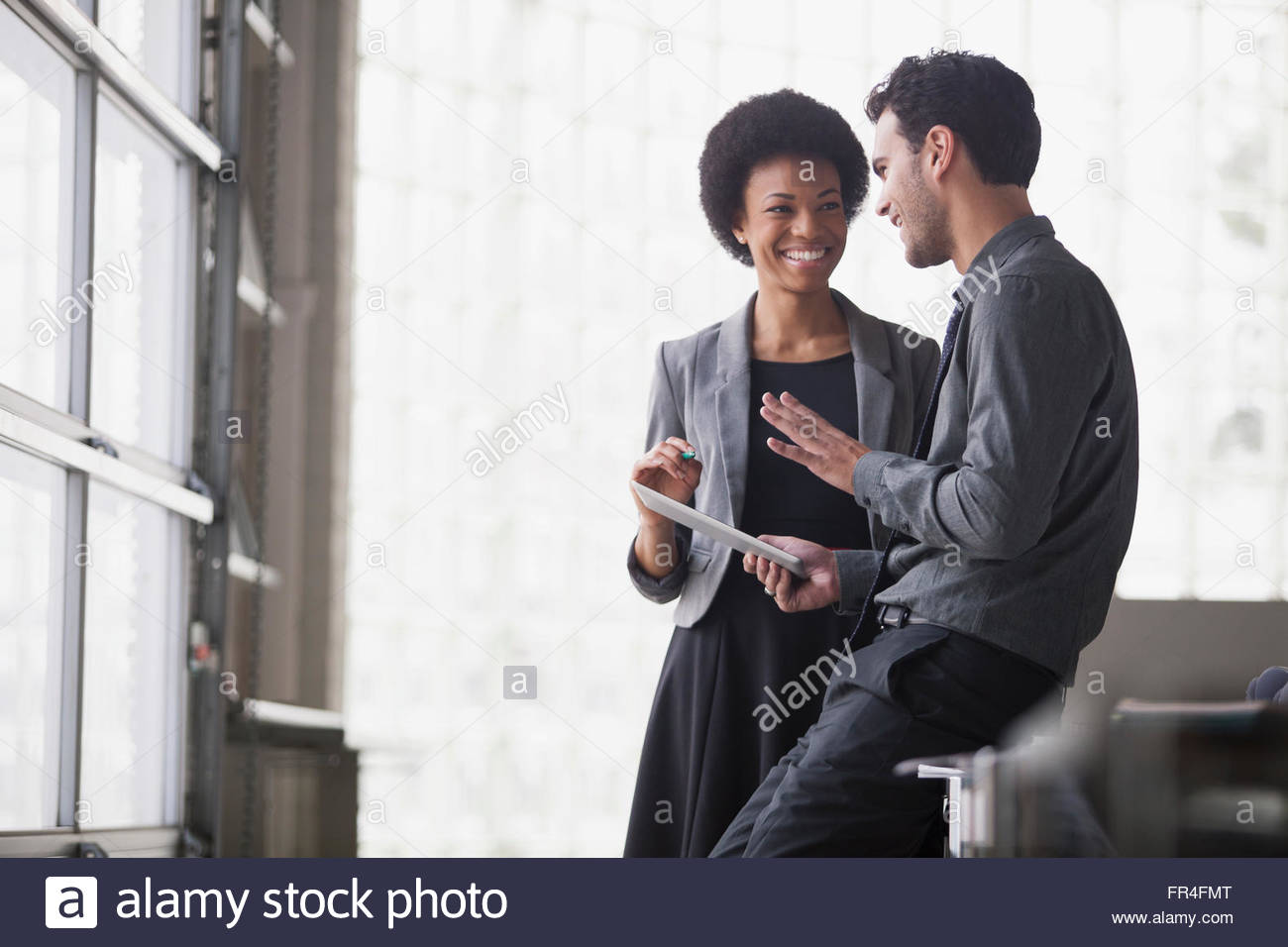 businessman holding tablet as he talks to female coworker - Stock Image