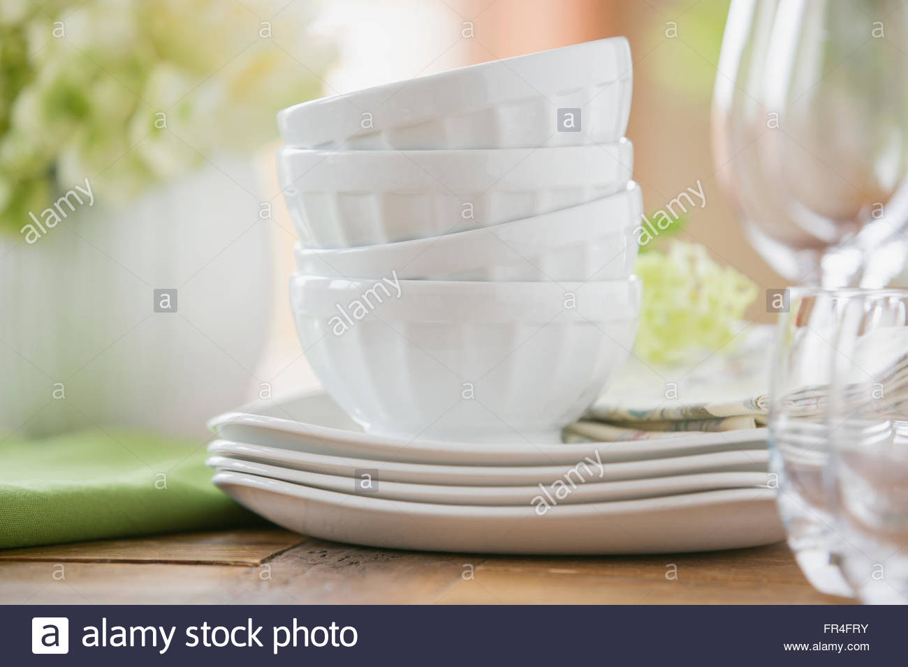 Stack of gleaming white bowls and plates. - Stock Image