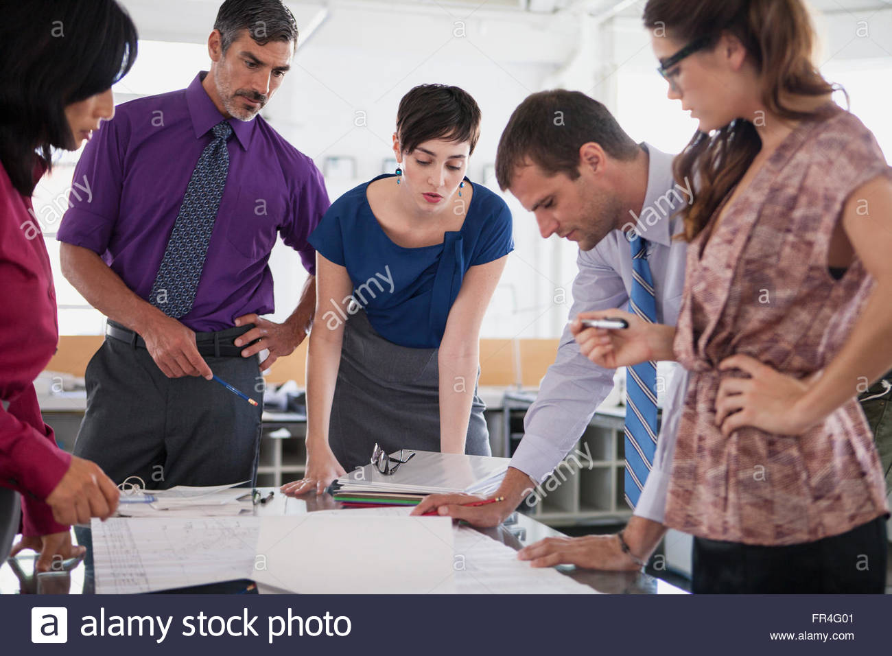 group of businesspeople reviewing blueprints - Stock Image