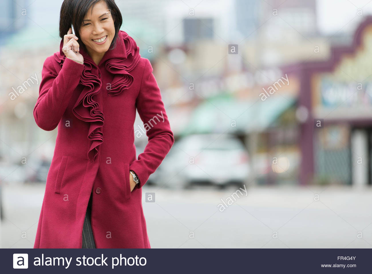 Asian woman walking on city sidewalk while talking on phone. - Stock Image