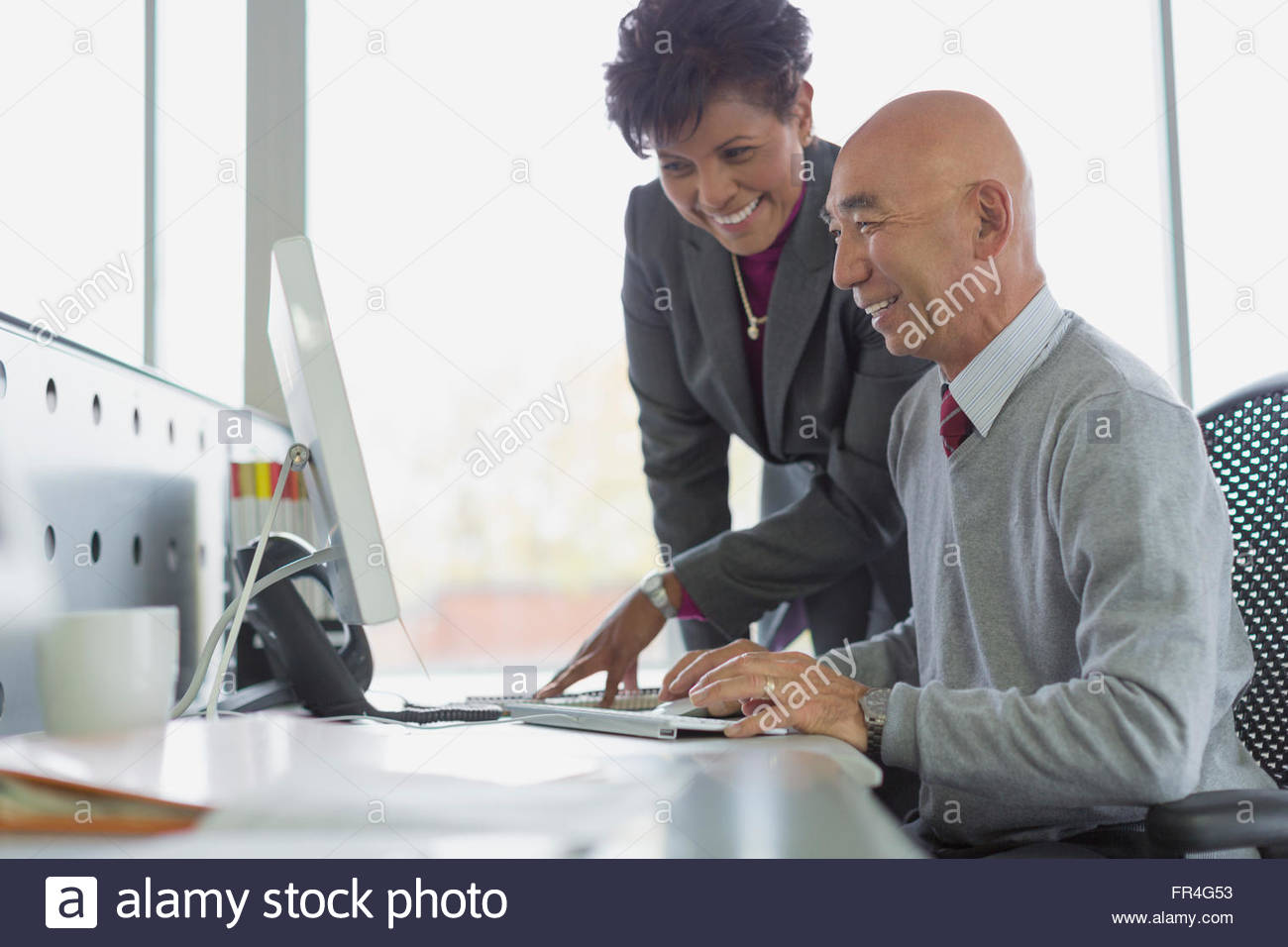 Co-workers smiling while looking at desktop computer. - Stock Image