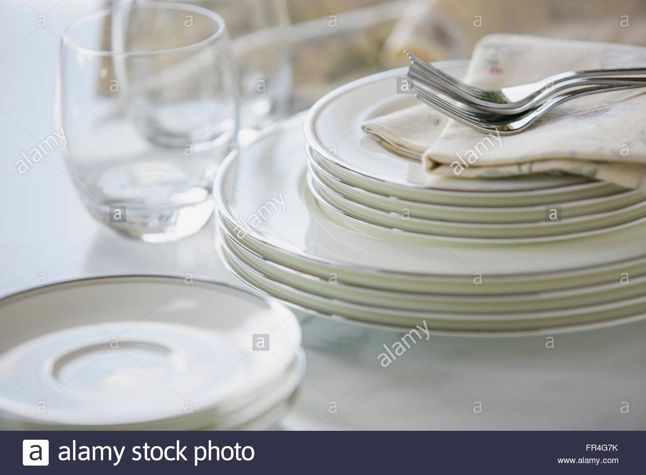 Close-up of gleaming fine china stacked on counter. - Stock Image