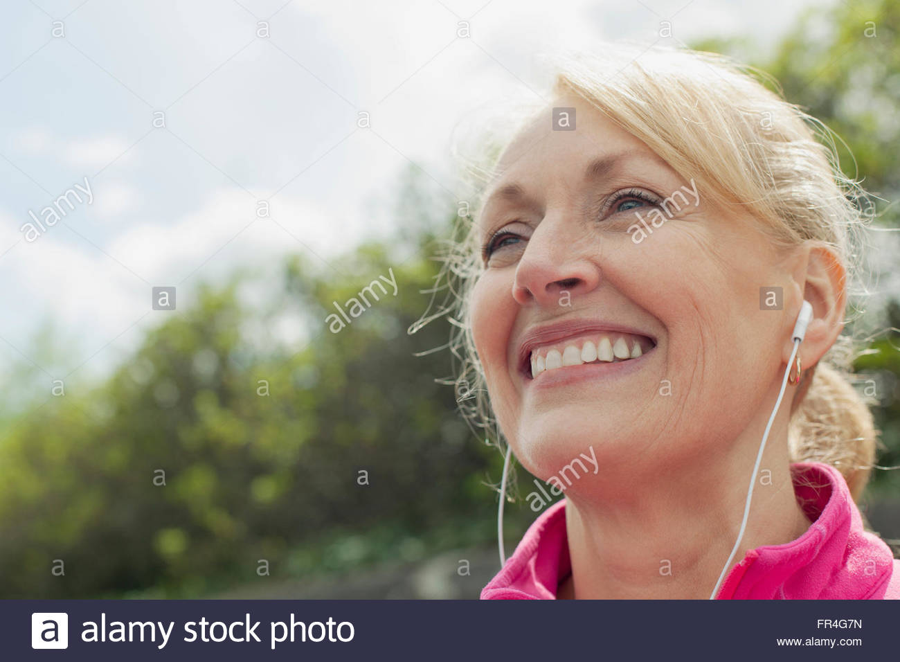 Close-up of senior woman with earphones. - Stock Image