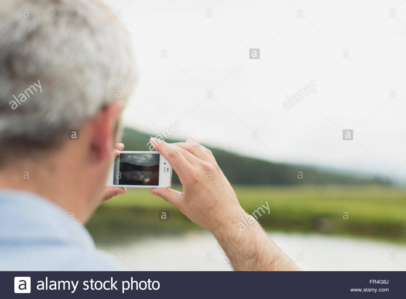 Close-up of man using smartphone to take picture. - Stock Image