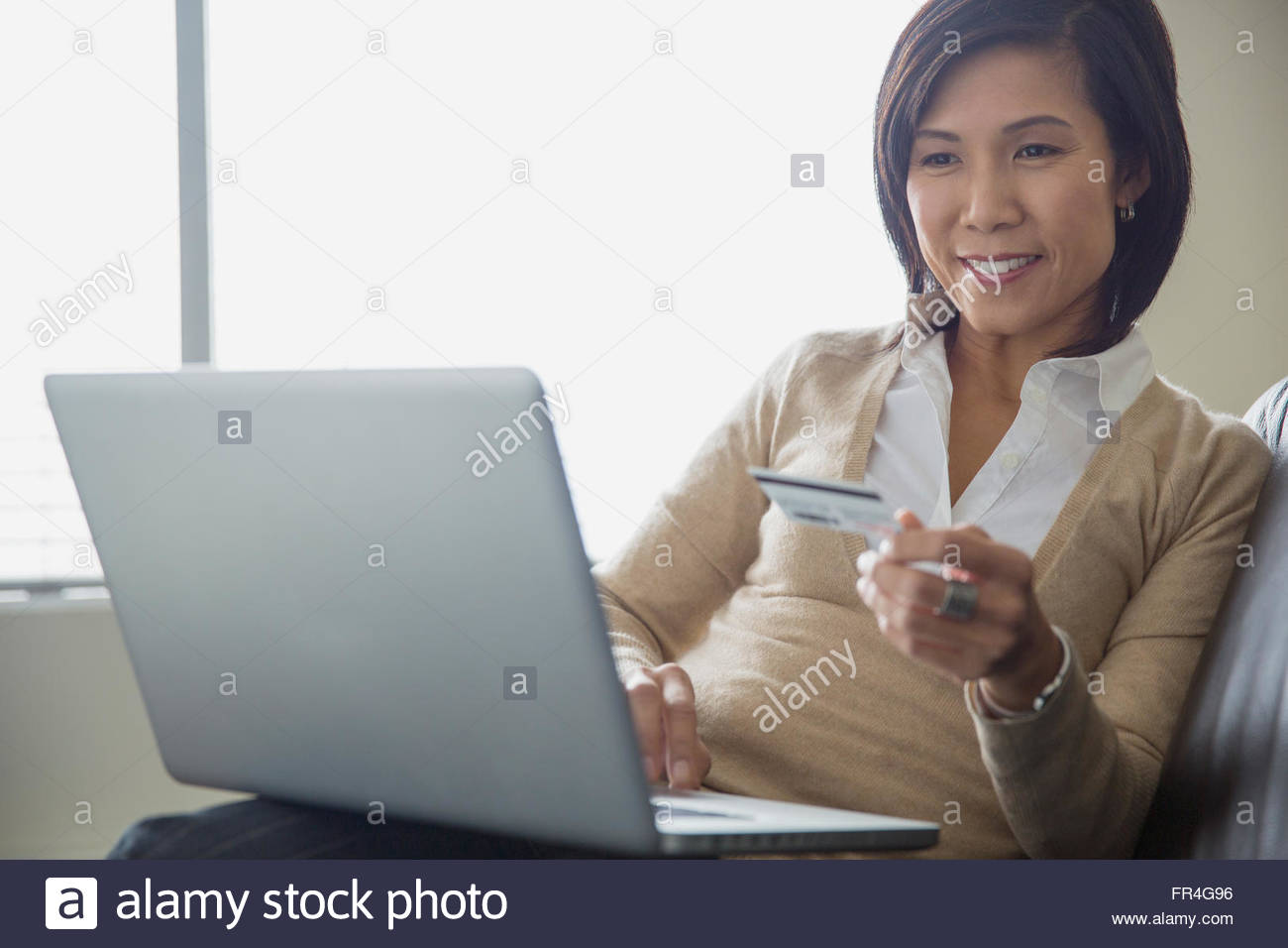 Asian woman making online purchase with credit card. - Stock Image