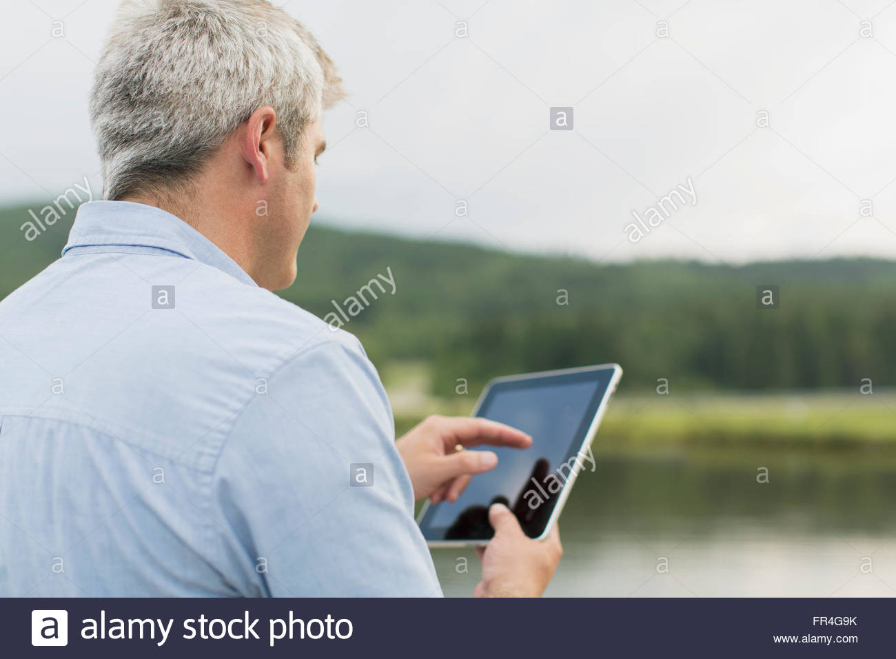 View from behind of middle-aged man using pc tablet. - Stock Image