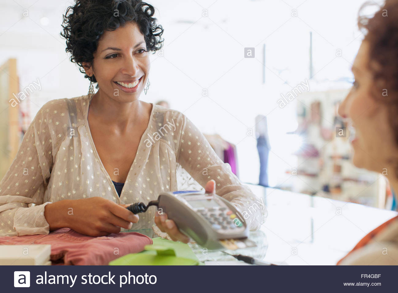 Sales clerk handing debit machine to customer. - Stock Image