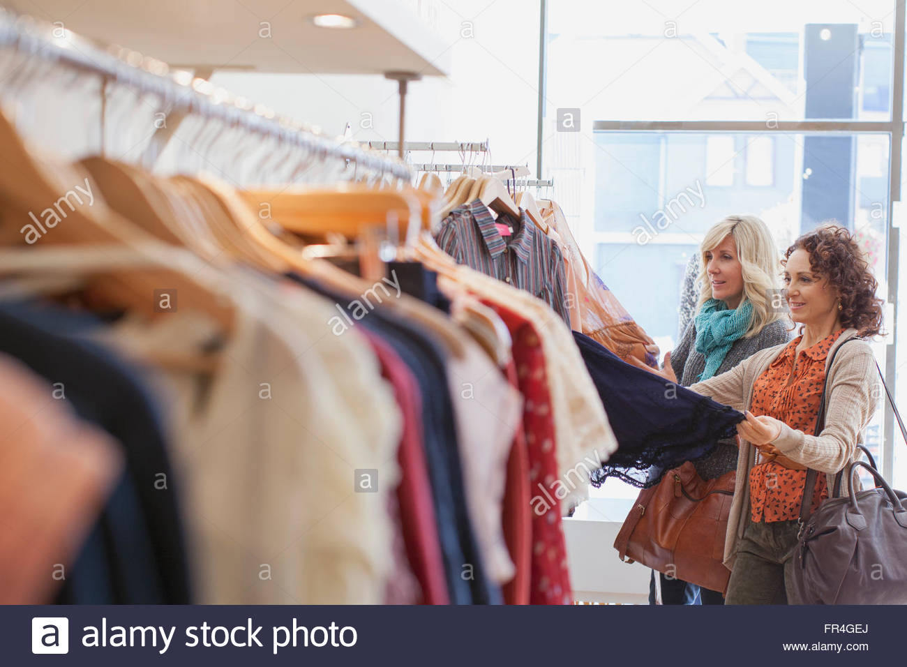 Friends looking at outfit in womens clothing store. - Stock Image
