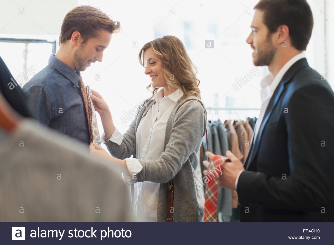 Sales clerk offering necktie options to couple. - Stock Image