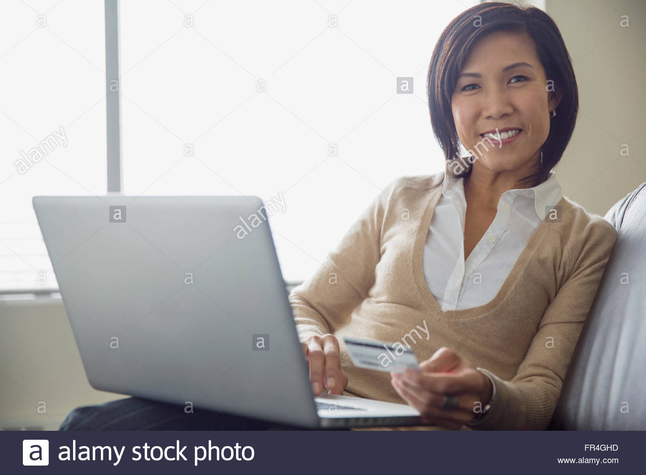 Portrait of Asian businesswoman making online purchase. - Stock Image
