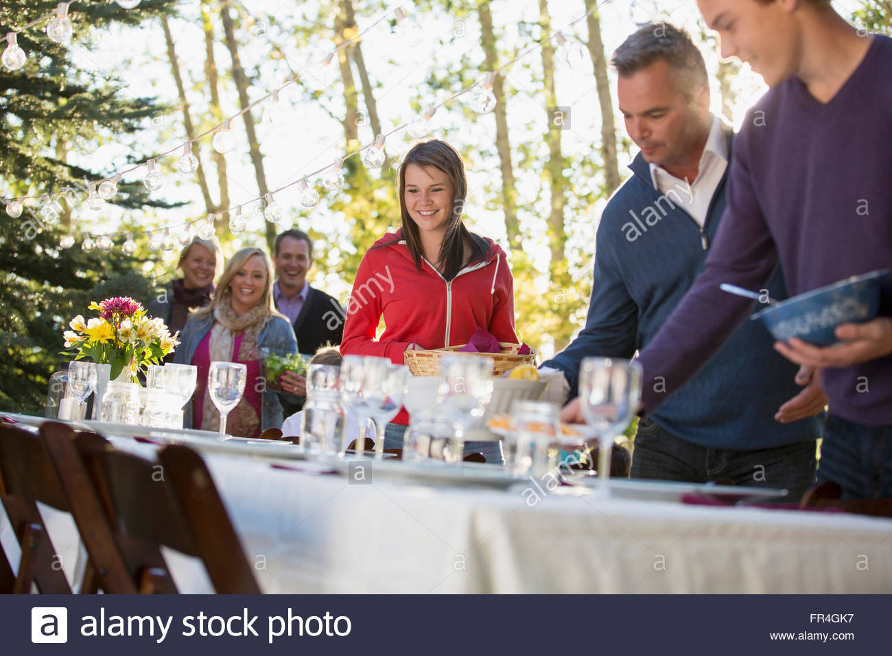 Family members lined up for buffet dinner outdoors. - Stock Image
