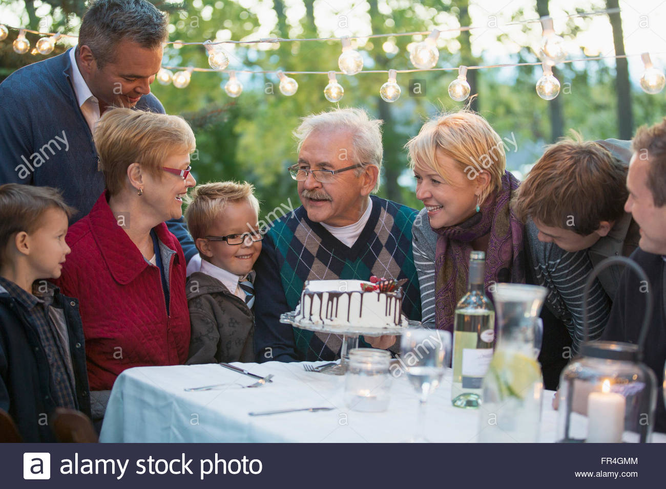 Family gathered around cake at outdoor dinner. - Stock Image