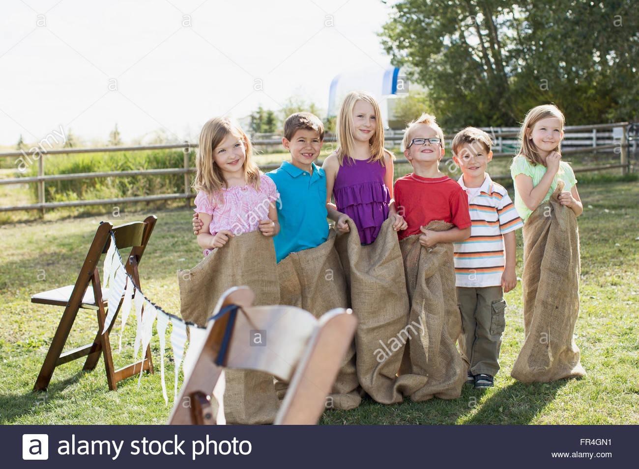 Sisters and cousins lined up for potato sack race. - Stock Image
