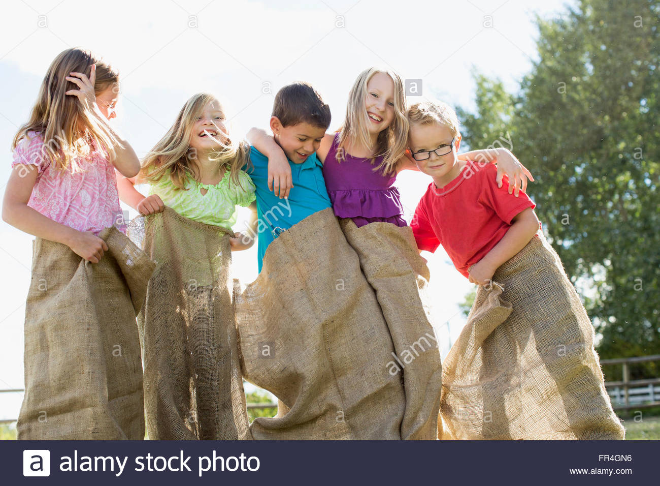Cousins getting ready for potato sack race. - Stock Image