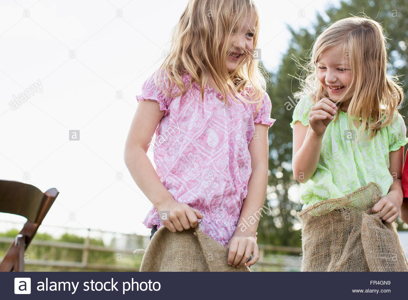 Twin sisters in a potato sack race. Stock Photo