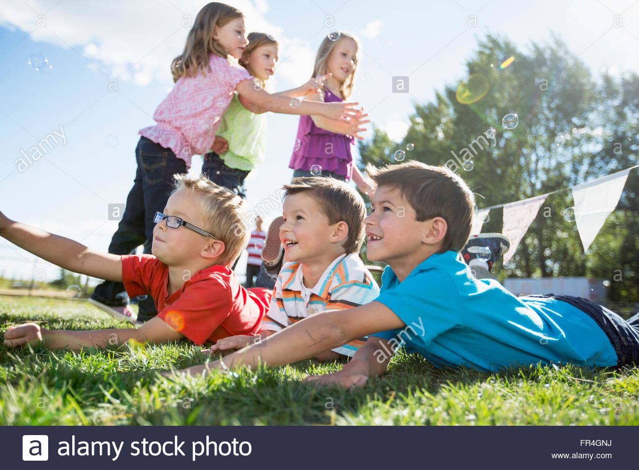 Kids chasing and catching bubbles outdoors. - Stock Image