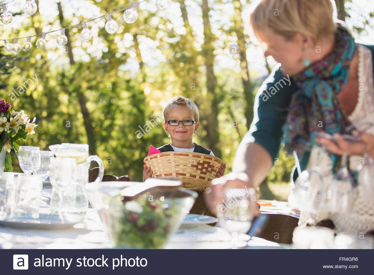 Six year old boy helping his mom to set an outdoor table. - Stock Image