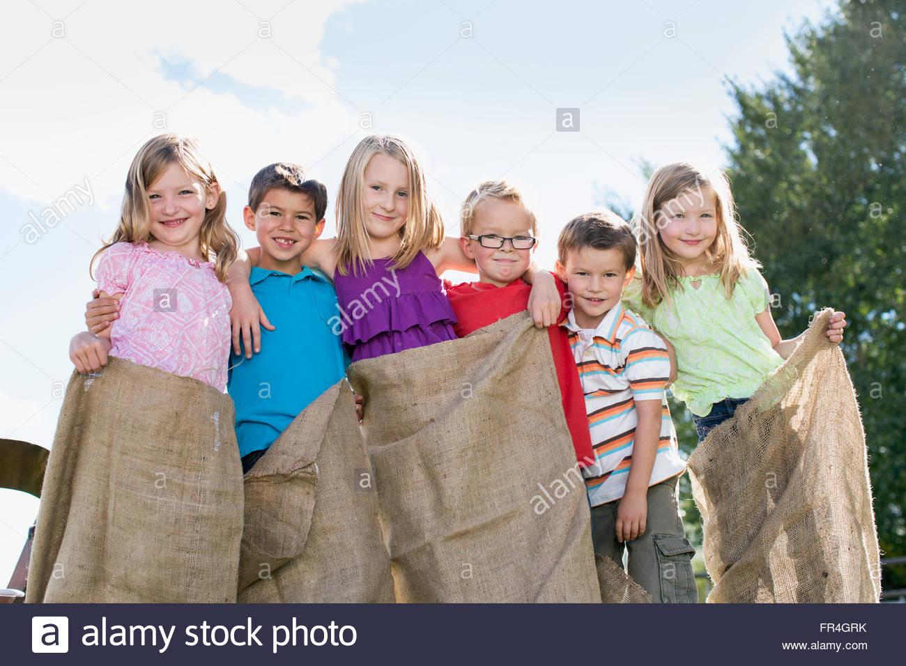 Cousins standing together with potato sacks on. - Stock Image