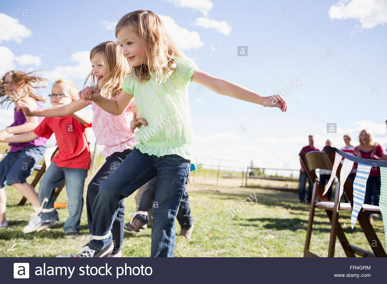 Children competing in 3 legged race at reunion. - Stock Image