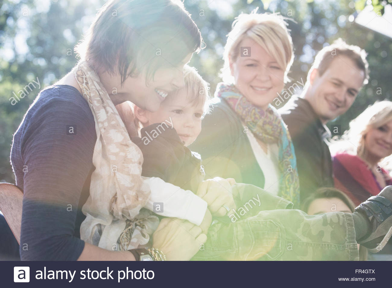 Mom holding two year old son at family reunion. - Stock Image