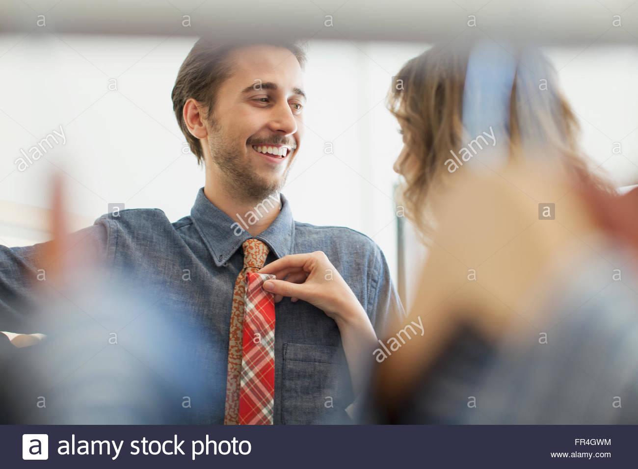 Girlfriend holding necktie option on boyfriends chest. - Stock Image