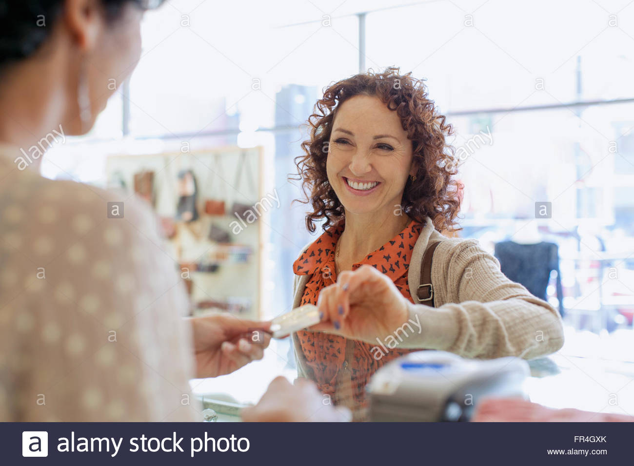 Customer handing credit card to sales clerk for payment. - Stock Image