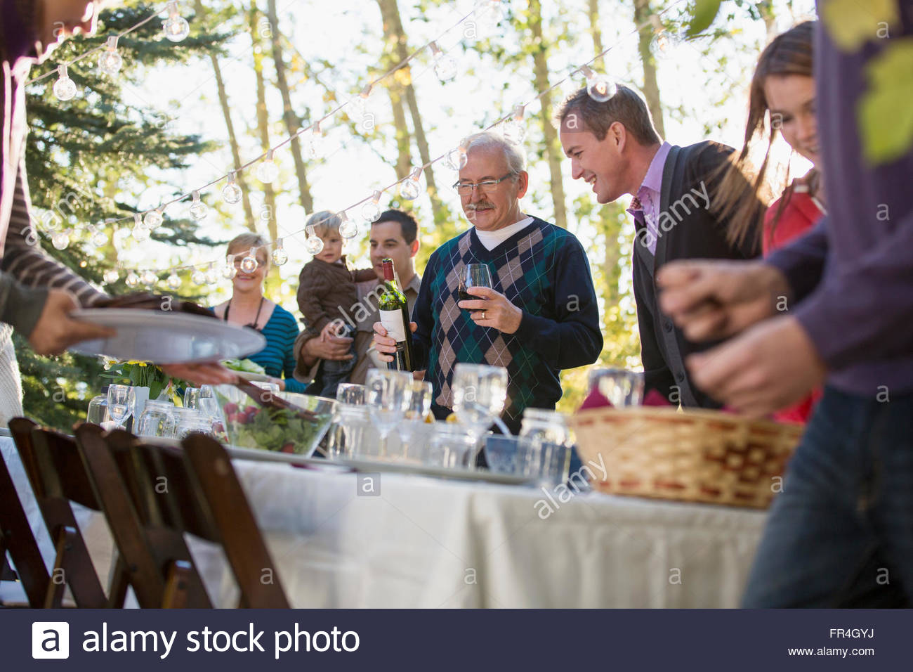 Family lined up for family reunion meal. - Stock Image