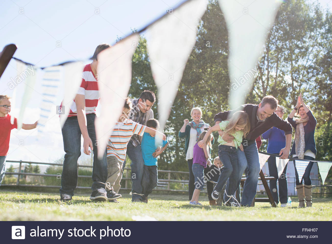 Family cheering family in 3 legged race event. - Stock Image