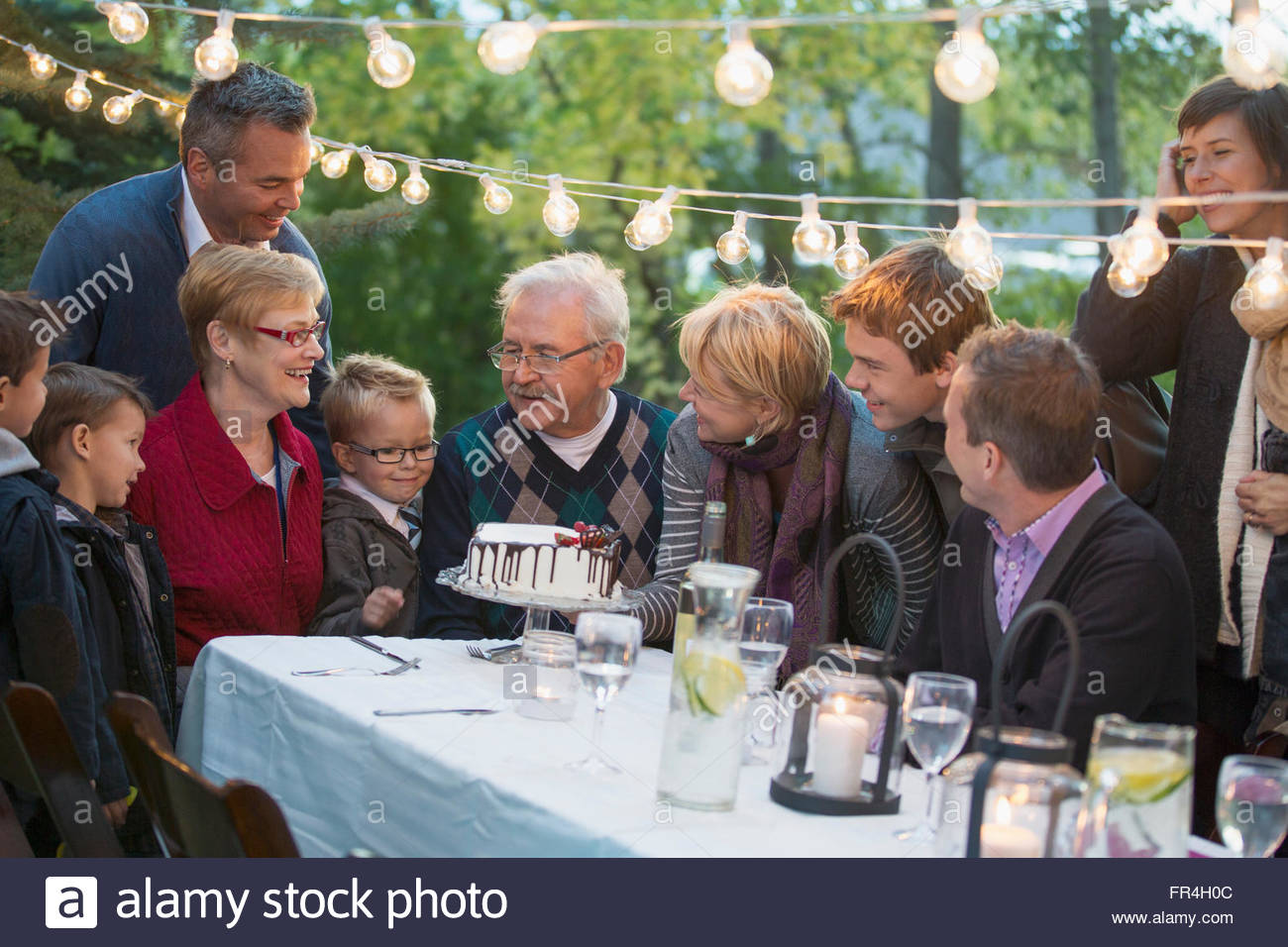 Family gathered around beautiful cake at outdoor dinner. - Stock Image