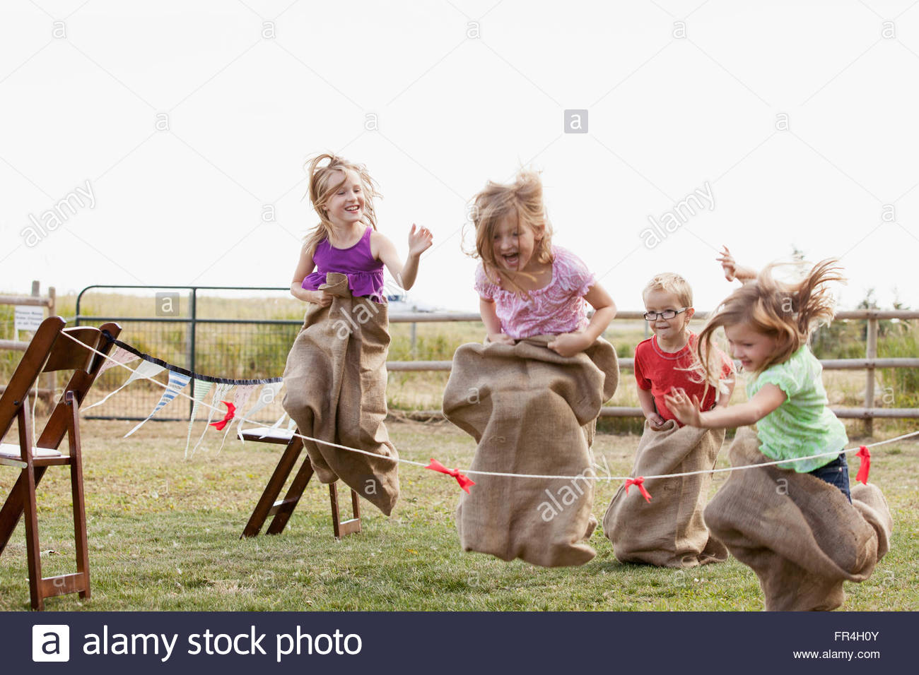 Cousins competing in potato sack race. - Stock Image