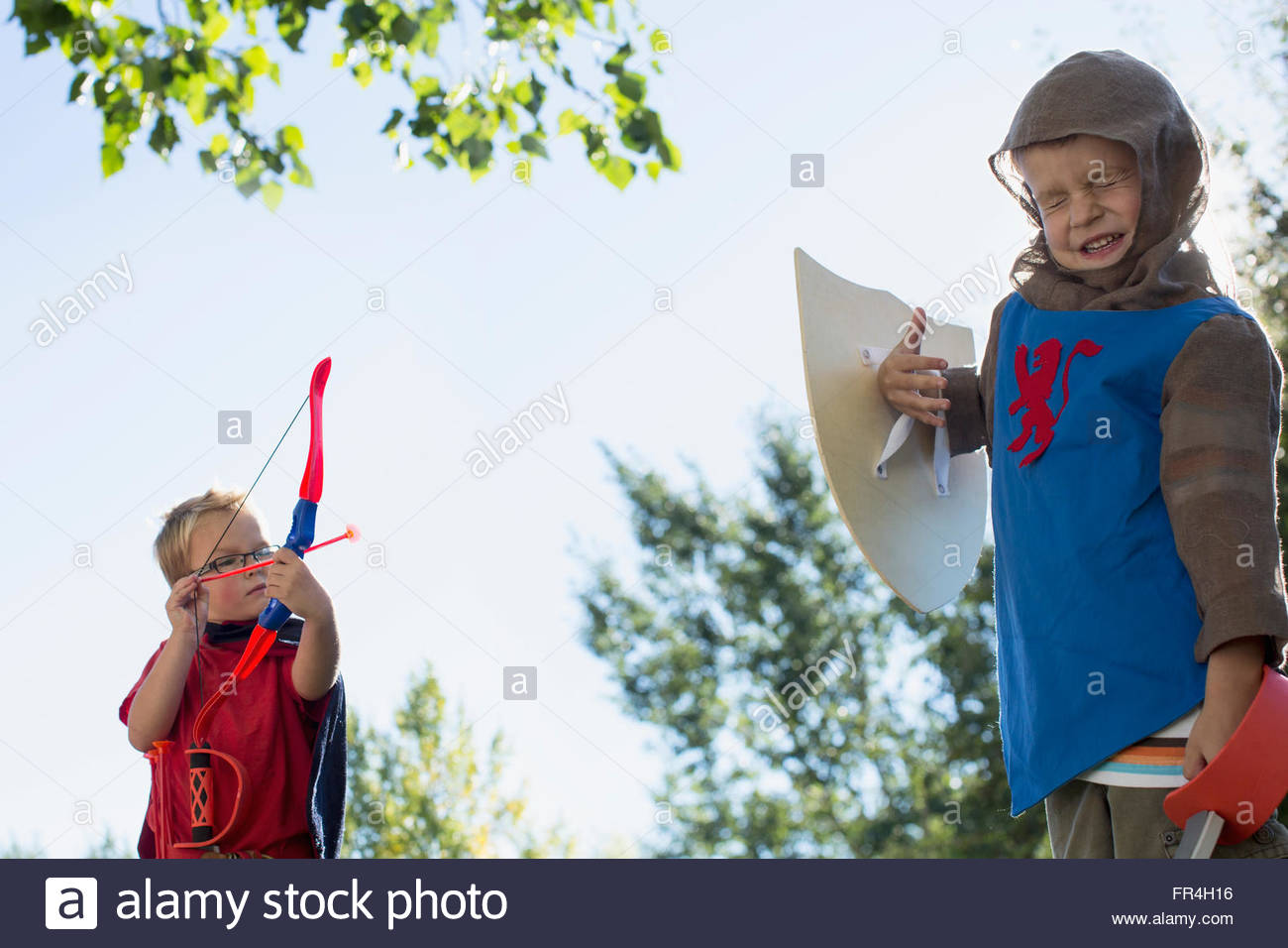 Young boys play fighting in costumes. - Stock Image
