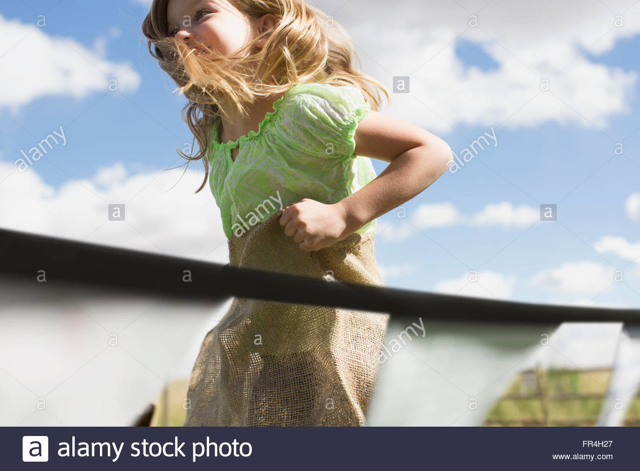 Young girl participating in a potato sack race. - Stock Image