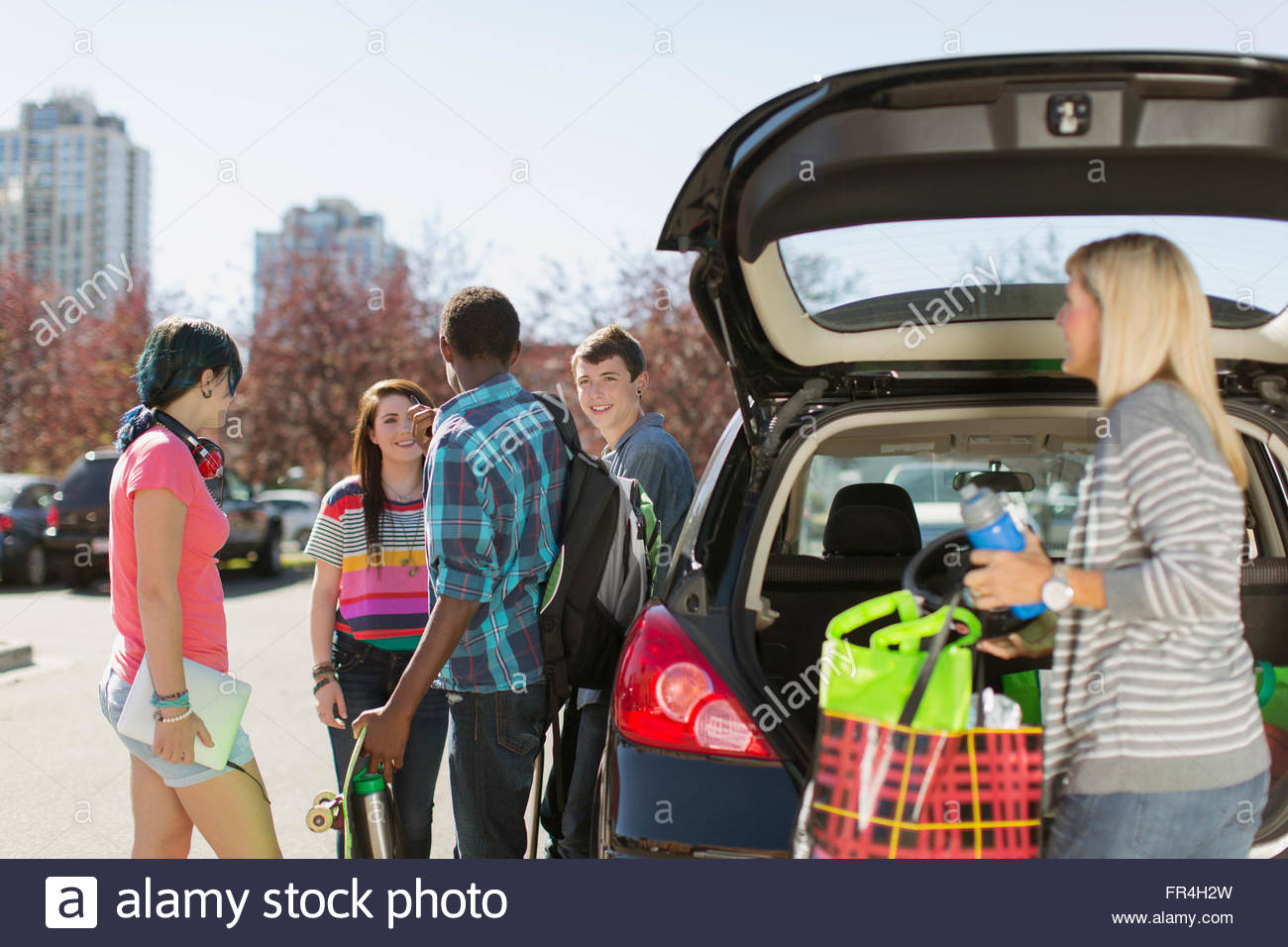 mom unloading supplies from hatchback for teenagers - Stock Image