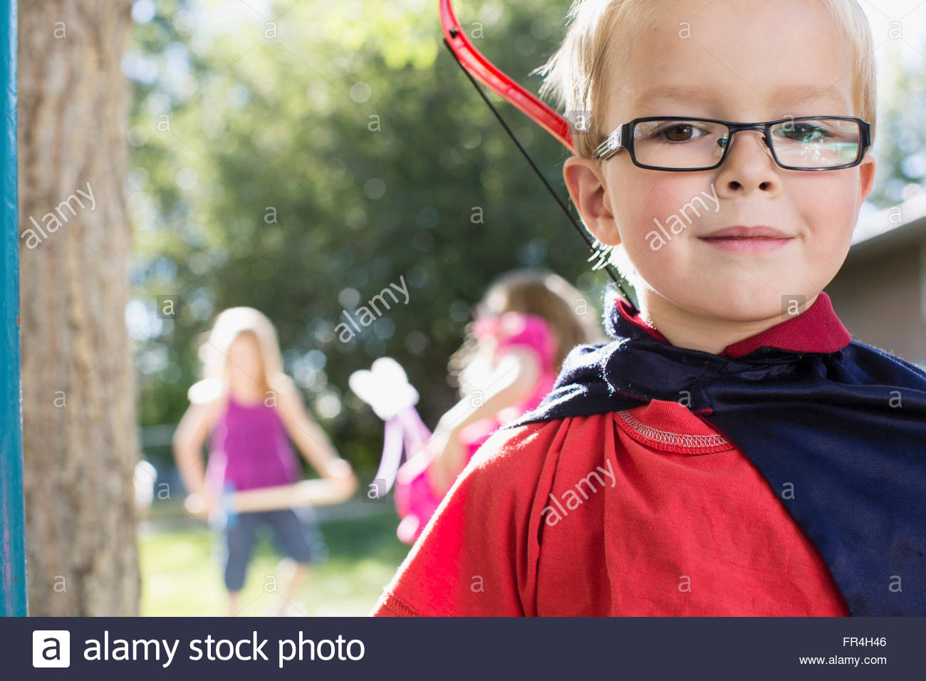 Portrait of six year old boy dressed in cape with bow and - Stock Image