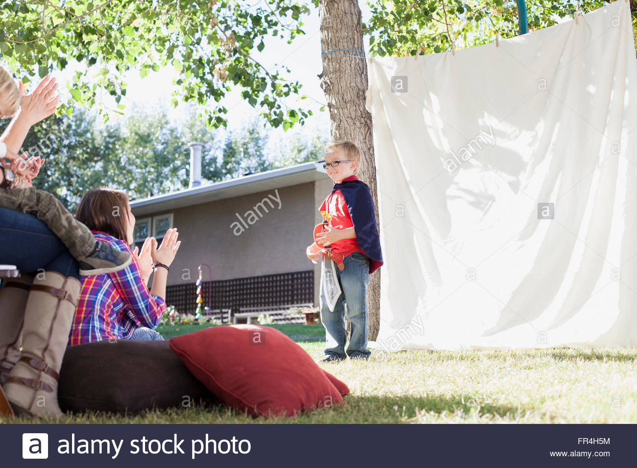Young boy performing a play for family. - Stock Image