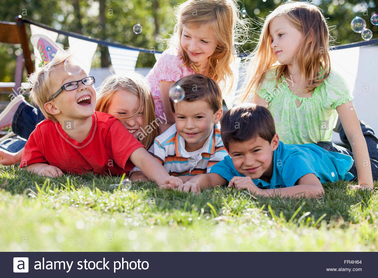 Cousins catching bubbles as they lie on the grass. - Stock Image