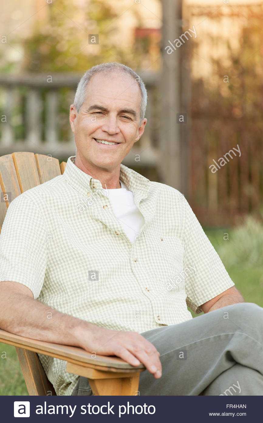 portrait of middle-aged man sitting outdoors - Stock Image