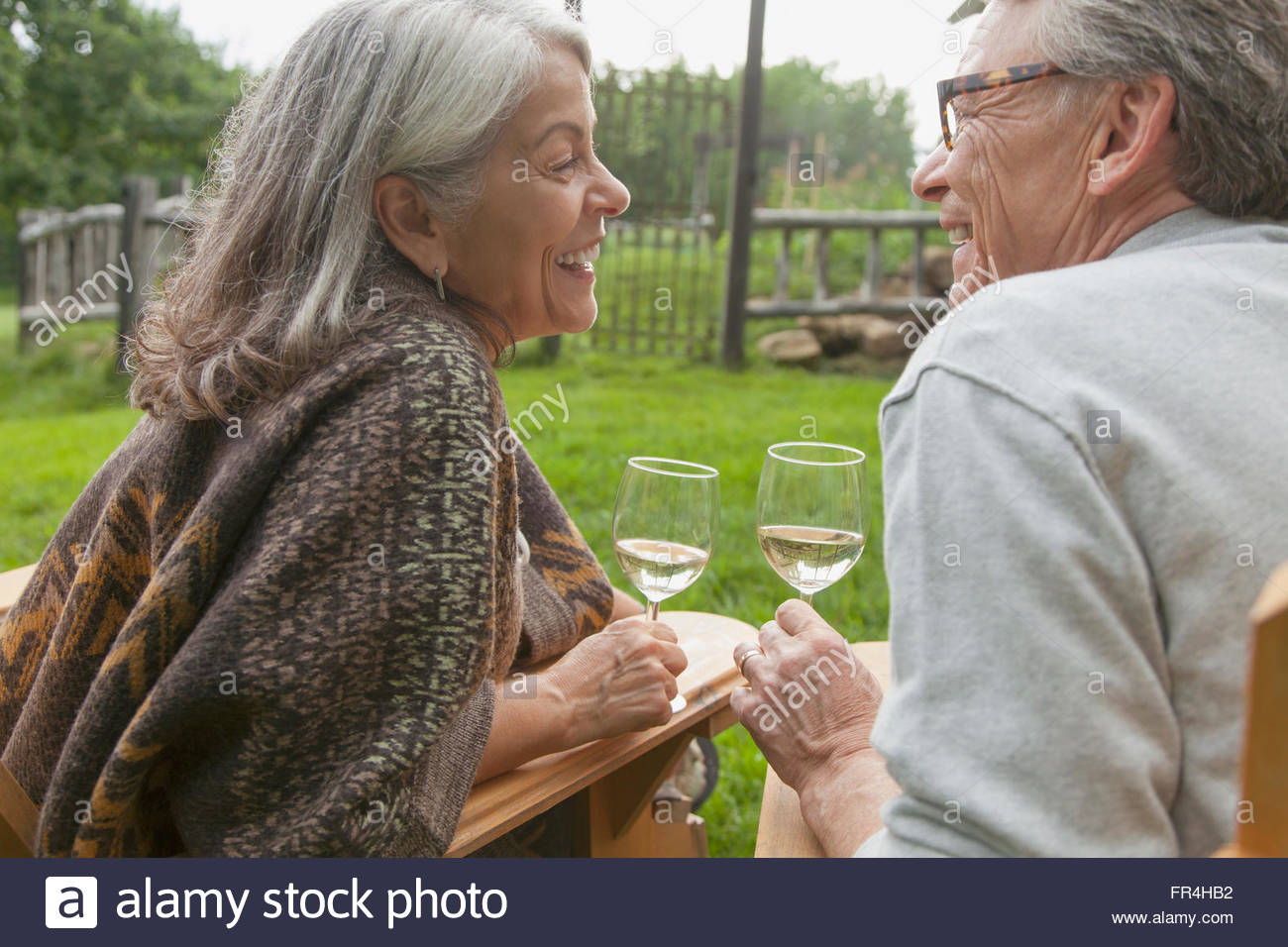 senior couple looking at each other while drinking wine - Stock Image